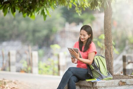 tab: A portrait of a young Asian student sitting outdoor using tablet pc