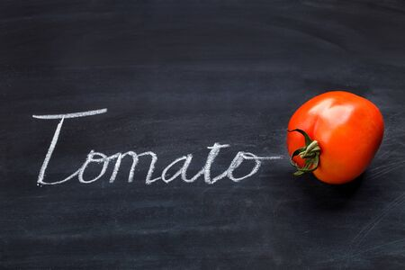 product: portrait of fresh tomato with inscriptions on black board