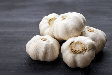 full frame portrait of fresh garlic on black board for table Фото со стока