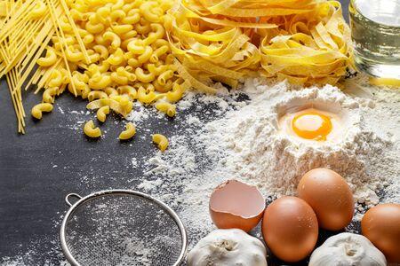 kulinarne: Portret domowego makaronu surowego włoskich i składniki na czarnej płycie