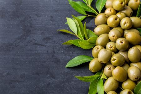 olive leaf: pila de aceitunas verdes en la tabla negro con espacio de copia Foto de archivo