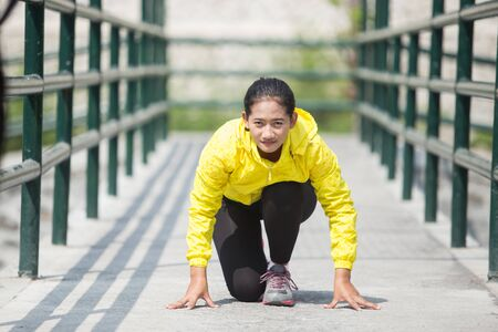 A portrait of a young asian woman exercising outdoor in yellow neon jacket, getting ready for sprinting