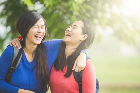 riendo: Un retrato de felices dos jóvenes estudiantes asiáticos reír, bromeando juntos