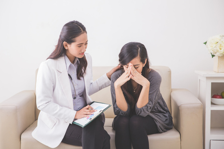 doctor examining woman: A portrait of Asian female patient crying while consulting her health problem with a female doctor Stock Photo
