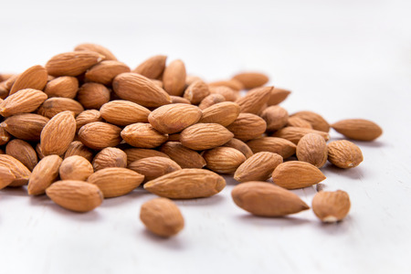 heap up: close up portrait of almonds in heap isolated on white background