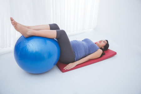 pregnant asian: A portrait of a beautiful asian pregnant woman doing exercise on yoga mat