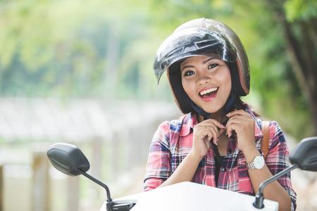 Ein Porträt einer jungen asiatischen Frau das Tragen eines Helmes vor ein Motorrad auf einem Park Reiten