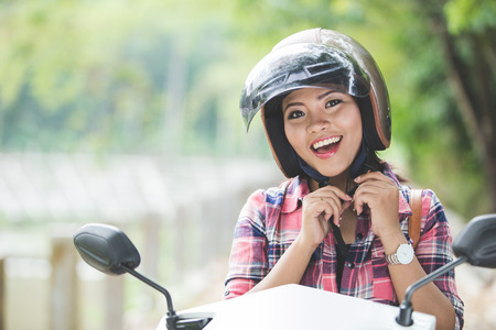 A portrait of a young asian woman wearing a helmet before riding a motorcycle on a park