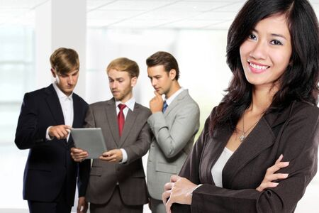 team from behind: A portrait of a young asian businesswoman, with her team behind isolated in white background