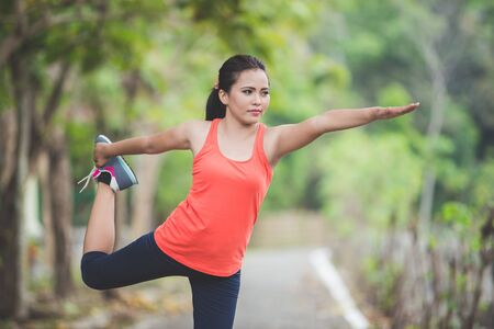 excercise: A portrait of a young asian woman doing excercise outdoor in a park, stretching