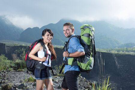 A portrait of a mixed couple go trekking together, nature background