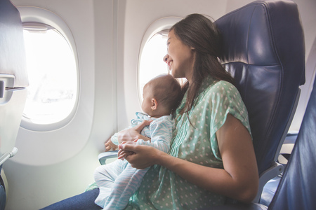 Glückliche Mutter und Kind zusammen in Flugzeugkabine nahe Fenster sitzt Standard-Bild - 50512395