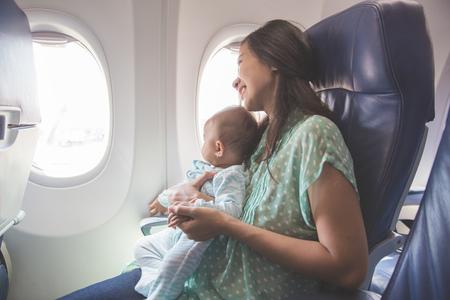 Madre y bebé felices sentados juntos en la cabina del avión cerca de la ventana Foto de archivo