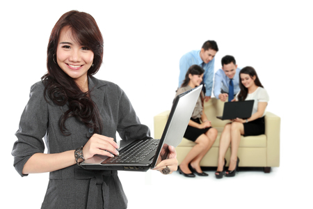 team from behind: A portrait of a young asian businesswoman, with her team behind holding laptop. isolated in white background Stock Photo