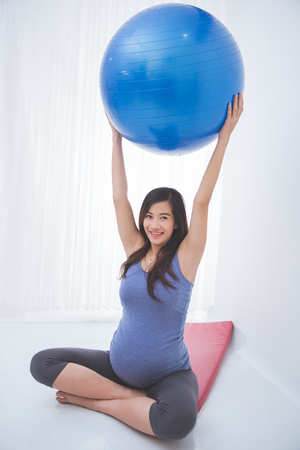 swiss ball: A portrait of a beautiful asian pregnant woman doing exercise with a yoga ball on yoga mat, smiling Stock Photo
