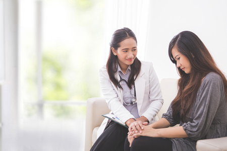 A portrait of Asian female patient crying while consulting her health problem with a female doctor Stock Photo