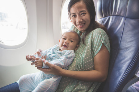 Happy mother and baby sitting together in airplane cabin near window