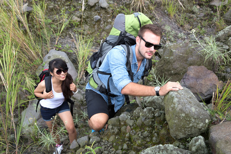 uphill: A portrait of a mixed couple go trekking together, walking on an uphill, nature background