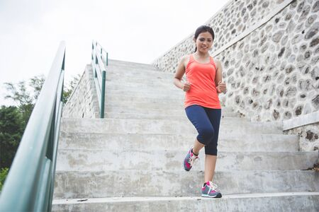 run down: A portrait of a young asian woman doing excercise outdoor in a park, jogging up and down the stair
