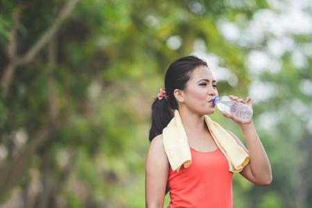 agua potable: Un retrato de una joven mujer asiática de agua potable después de hacer ejercicio al aire libre en un parque