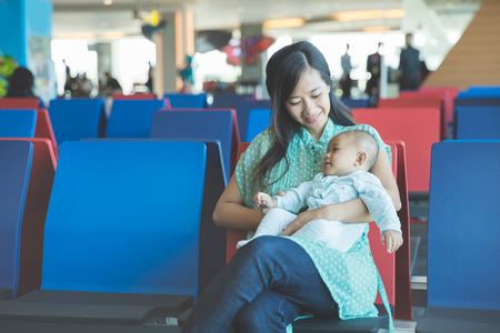 portrait of cute little baby waiting in the airport with her mother