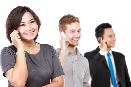 llamando: Un retrato de una mujer feliz de negocios maduros hablando por teléfono, con su personal detrás