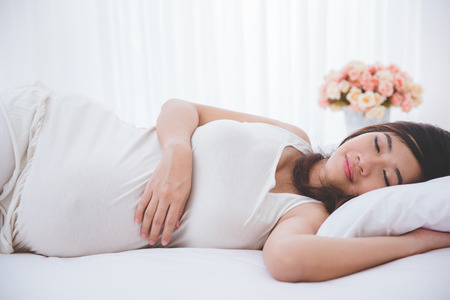 A portrait of a beautiful asian pregnant woman sleeping peacefully