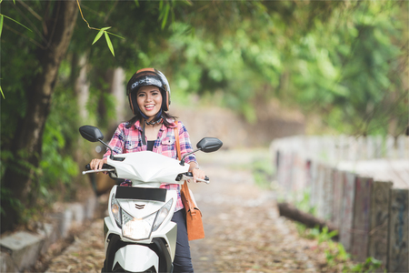 A portrait of a young asian woman riding a motorcycle in a park Standard-Bild