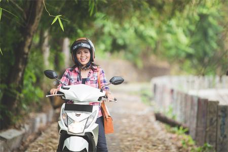 Un retrato de una mujer asiática joven en una motocicleta en un parque Foto de archivo
