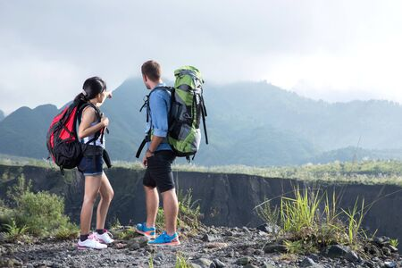 mixed couple: A portrait of a mixed couple go trekking together, nature background