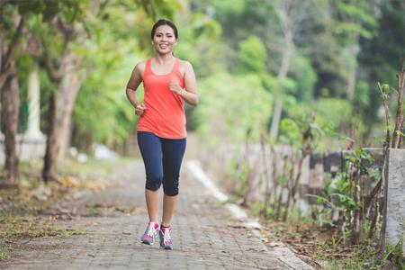Een portret van een jonge Aziatische vrouw doen oefening buiten in een park, joggen
