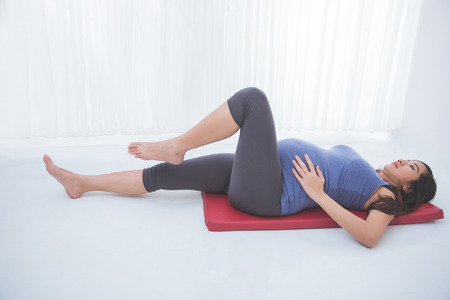 pregnancy exercise: A portrait of a beautiful asian pregnant woman doing exercise on yoga mat