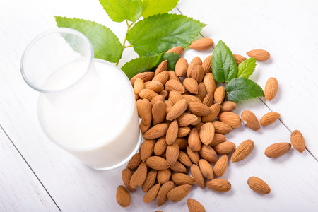 portrait of a bottle of fresh almond milk with a pile of almond isolatewd on white background Archivio Fotografico