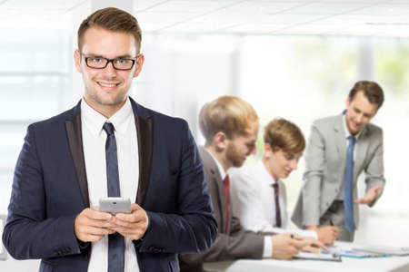 team from behind: A portrait of a young caucasian businessman, with his team behind holding cellphone Stock Photo