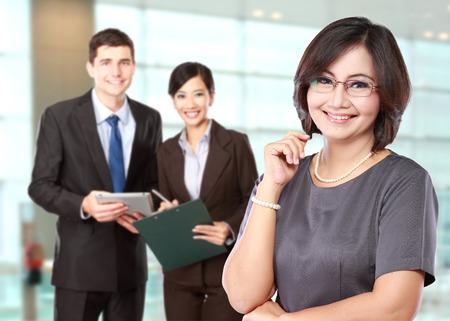 Un retrato de una mujer feliz de negocios maduros con su personal detrás Foto de archivo