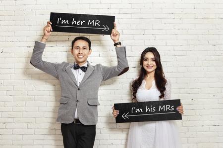 ハンサムな新郎と背景が白い壁のボードを押しながら笑みを浮かべて美しい花嫁の肖像画