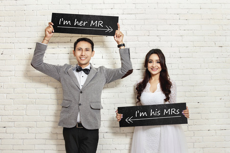 portrait of handsome groom and beautiful bride smiling while holding board with white wall background