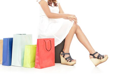 female legs: portrait of woman sitting next to shopping bags isolated on white background