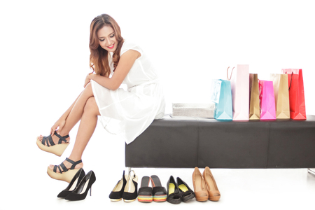 full body portrait of elegant woman sitting next to shopping bags and pairs of shoes isolated on white background