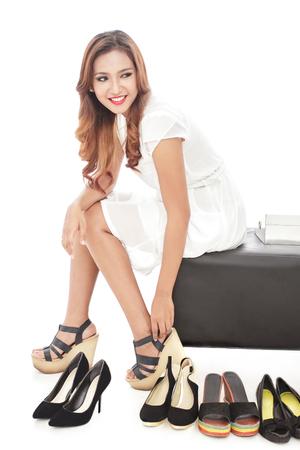 comprando zapatos: retrato de una mujer joven y atractiva que intenta en varios pares de zapatos nuevos aislados sobre fondo blanco