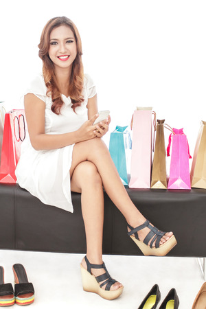shoes woman: full body portrait of beautiful woman sitting between shopping bags while holding mobilephone isolated on white background