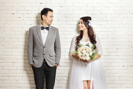 흰 벽 배경으로 서로를 쳐다보고 아름다운 신부와 잘 생긴 신랑의 전신 초상화