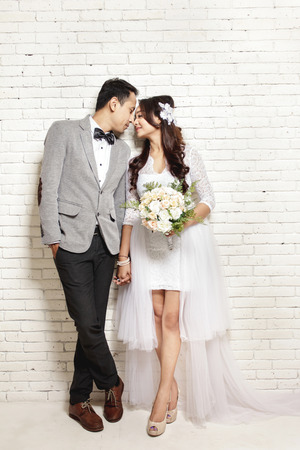 full body portrait of lovely asian newlywed couple with white wall background