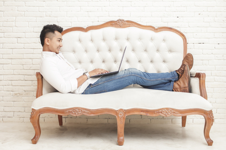 man sit: full view photo asian young man sitting relax on sofa while working on laptop at home Stock Photo
