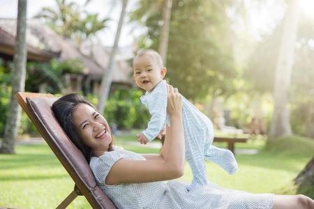 madre e hijo: retrato de una madre hermosa asiática se divierte con su bebé en un día soleado Foto de archivo