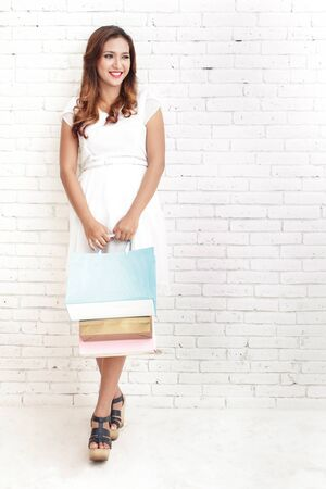 hang body: full body portrait of young woman smiling while carrying shopping bags with white brick wall on the background