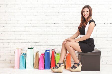 mujer sentada: retrato de mujer joven sonriente y sentado junto a bolsas de compras en el fondo multicolor pared de ladrillo blanco Foto de archivo
