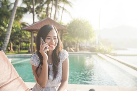 young beautiful woman calling using mobile phone while relaxing next to the pool