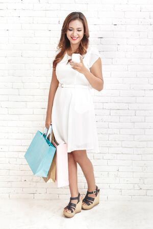 asian lifestyle: young woman smiling while carrying shopping bags Stock Photo