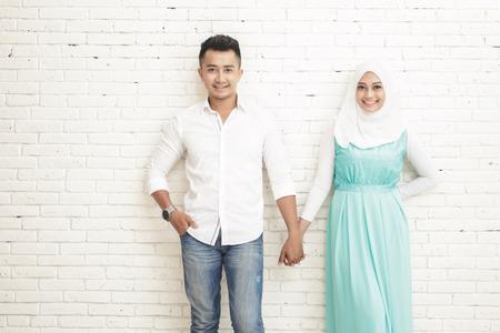 manos entrelazadas: Retrato de la romántica pareja asiática de pie y sonriente mientras sostiene entre sí las manos